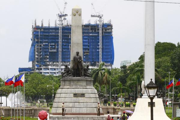 The Torre de Manila under construction seen behind the Rizal Monument