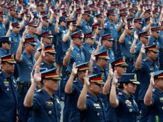 Police officers take their oath at the Philippine National Police headquarters in Quezon