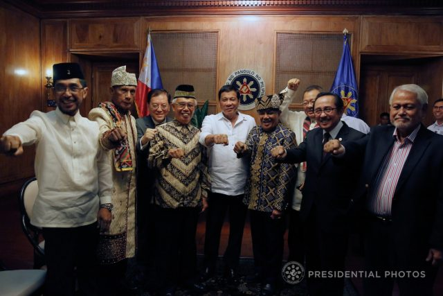 President Rodrigo Roa Duterte does his signature pose with Abdaham Idjirani, Sultan Phudalun Kiram II, Dr. Charles Chan, Datu Michael Ong Mastura, Sultan Omar Pax Mangudadatu, Pastor Saycon, Mindanao Development Authority Chair Datu Abul Khayr Alonto and Special Envoy to the Organization of Islamic Cooperation Alamarim Tillah during a meeting at the Malacañan Palace on October 12, 2017. ROLANDO MAILO/PRESIDENTIAL PHOTO