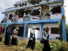 Marawi_walking_past_ruined_house-648_REU