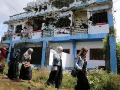 Marawi_walking_past_ruined_house-648_REU