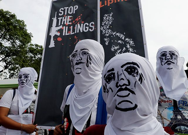 Activists wear hoods depicting families of victims killed in President Rodrigo Duterte's drug war as Duterte delivers his State of the Nation address in Quezon city, Metro Manila