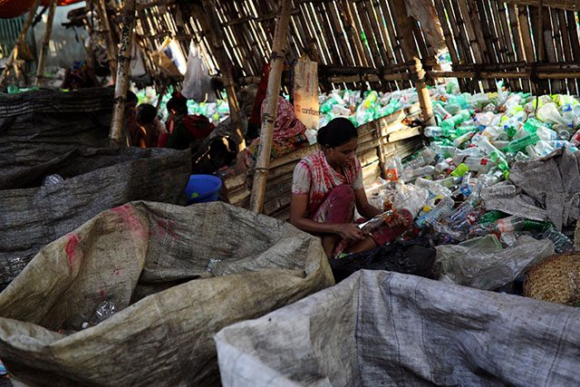 A woman works in a plastic bottle recycling factory in Dhaka