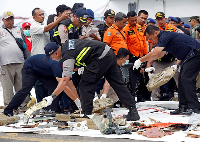 Rescue workers lay out newly recovered debris