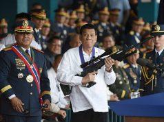 Philippine President Rodrigo Duterte holds a Galil sniper rifle next to outgoing Philippine National Police Chief Ronald Bato Dela Rosa during the National Police chief handover ceremony in Camp Crame