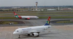 A South African Airways Airbus A320 aircraft arrives as a Kenya Airways Boeing 737 aircraft prepares to take off at the OR Tambo International Airport in Johannesburg