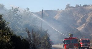 Firefighter sprays water from a fire truck