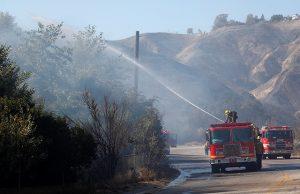 Firefighter sprays water from a fire truck
