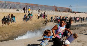 A migrant family runs away from tear gas