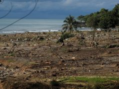 Debris is seen along a beach after a tsunami, near Sumur