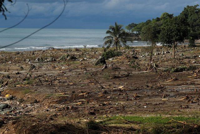 Debris is seen along a beach after a tsunami, near Sumur