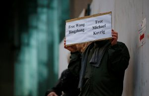 A man holds a sign calling for China to release Wang Bingzhang and former Canadian diplomat Kovrig, who was arrested in China on Tuesday, outside the B.C. Supreme Court bail hearing of Huawei CFO Meng Wanzhou