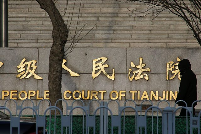 A man walks past the courthouse where prominent rights lawyer Wang Quanzhang is being tried in Tianjin