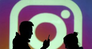 Silhouettes of mobile users are seen next to a screen projection of Instagram logo in this picture illustration