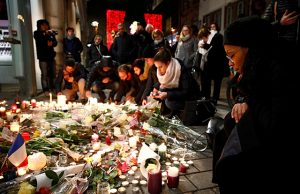 People cry as they light candles in tribute to the victims of the deadly shooting in Strasbourg