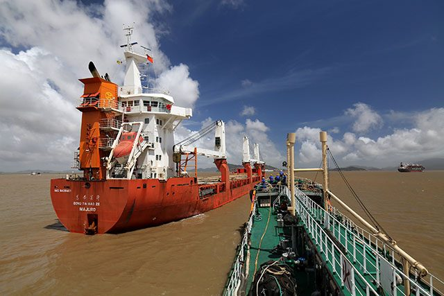 Sinopec oil tanker approaches cargo vessel Dongtai Baoze berthed at an anchorage off Zhoushan port to supply it with bunker fuel