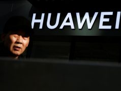 A man walks past a Huawei phone retail shop in Beijing