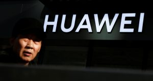 A man walks past a Huawei phone retail shop in Beijing