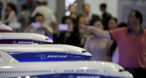 FILE PHOTO: Visitors look at models of Boeing aircrafts at the Aviation Expo China, in Beijing, China