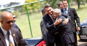 Brazil's President Jair Bolsonaro is greeted by Augusto Heleno, Minister of Institutional Security, before meeting at the Secretariat of Security and Coordination Presidential Cabinet in Brasilia