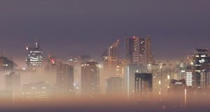 The Metro Manila skyline is seen during smog on the first break of dawn of the New Year in Antipolo City, Rizal