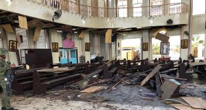 Philippine Army member inspects damage inside church after bombing attack in Jolo