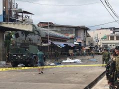 Philippine Army members secure area outside a church after bombing attack in Jolo