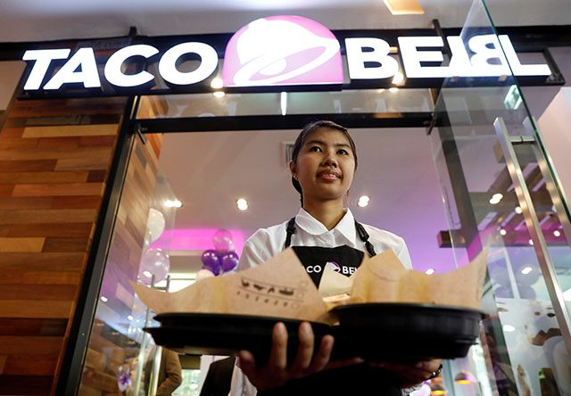 Server presents food during Taco Bell restaurant opening