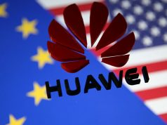 A 3D printed Huawei logo is placed on glass above displayed EU and US flags in this illustration