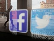 Facebook and Twitter logos are seen on a shop window in Malaga