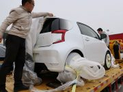 Singulato workers unwrap a concept car in preparation for the auto show in Shanghai