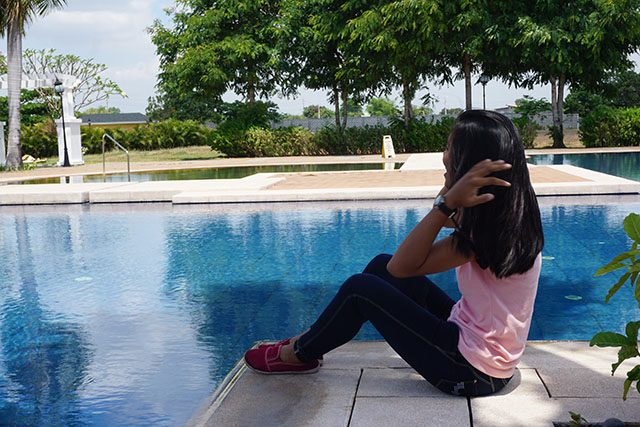 Chang, a young survivor of online child sex abuse, looks out over the pool at a private residence in Pampanga, the Philippines, April 5, 2019. Thomson Reuters Foundation/Matt Blomberg