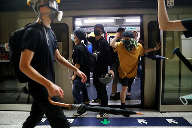 Protesters hold the door of a Mass Transit Railway (MTR) subway to allow more protesters to board and retreat, after a protest against police violence in Hong Kong