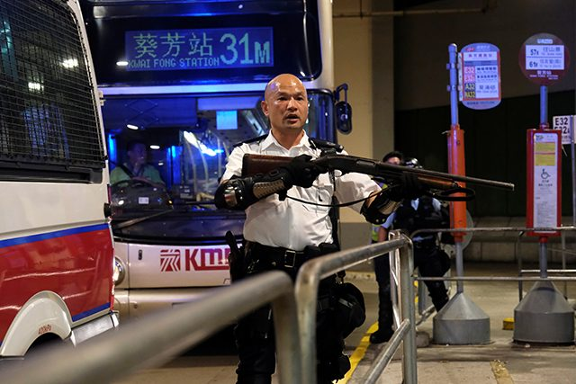 A police officer points a gun during clashes with anti-extradition bill protesters who surrounded a police station where detained protesters are being held, in Hong Kong