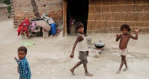 Children showing signs of malnutrition play outside their home in Marwan village