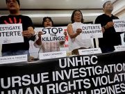 Members of the human rights groups hold banners calling to investigate Philippine President Rodrigo Dutere