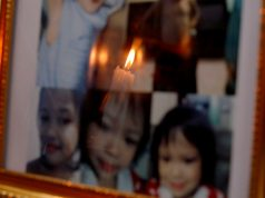 Candle is reflected off framed photos of 3-year-old Ulpina at her wake in Rodriguez, Rizal province