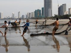Vietnamese fishermen pull the fishnets on a beach in Da Nang city