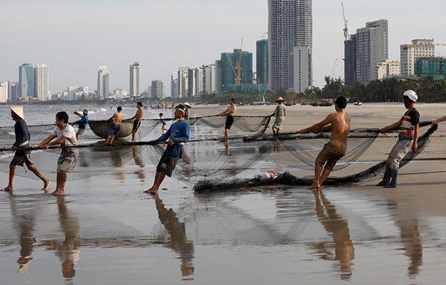 Vietnamese fishermen pull the fishnets on a beach in Da Nang city