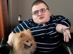 Online message board 8chan creator Fredrick Brennan gestures while sitting with a pet dog during an interview in Manila