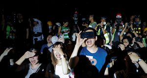 Demonstrators react as riot police point strong flashlights to their face after an anti-extradition bill protest in Hong Kong