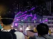 Anti-extradition bill protesters watch as demonstrators point laser pens at the police station in Sham Shui Po in Hong Kong