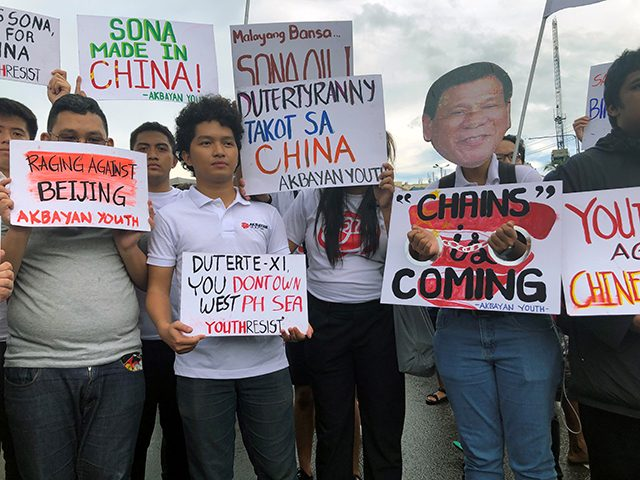 Filipino student activists hold placards against China during a protest against Duterte's annual State of the Nation Address in Manila