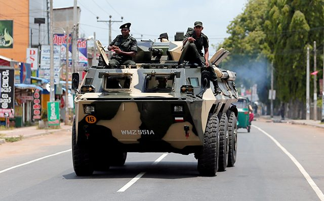 Sri Lankan soldiers patrol a road of Hettipola after a mob attack in a mosque in the nearby village of Kottampitiya