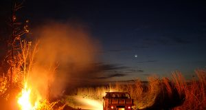 A fire burns a tract of the Amazon jungle as a truck goes by, in Areoes, Mato Grosso state