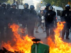 Riot police officers stand next to a burning barricade during a protest urging authorities to take emergency measures against climate change, in Paris