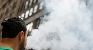 A man uses a vape as he walks on Broadway in New York City