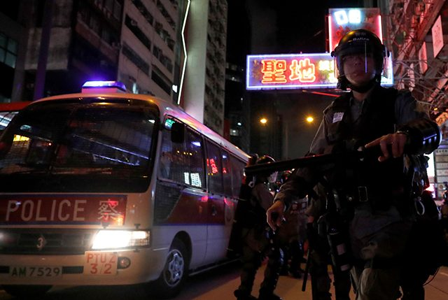 Riot police patrol streets near Mong Kok police station during an anti-extradition bill protest, in Hong Kong