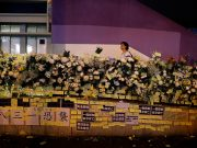 People pay their respects to the protesters who were injured during clashes with the police by placing flowers outside Prince Edward station, in Hong Kong