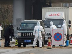 Workers in protective suits are seen at a checkpoint near a farm where African swine fever was detected